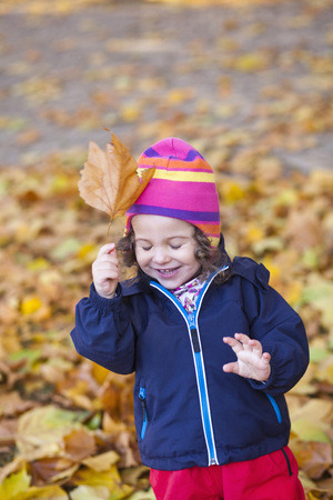 whimsy: Happy baby girl playing with maple leaf at park