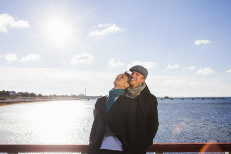 beings: Happy gay couple standing together on a jetty LANG_EVOIMAGES
