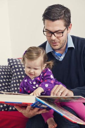 beings: Mid adult man sitting with premature daughter pointing at book
