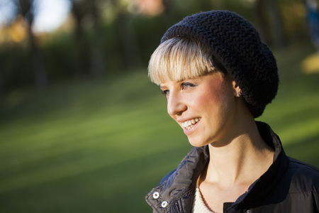 Side view of happy young woman in knit hat at park