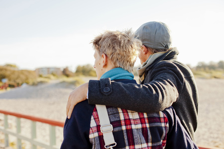 Rear view of young male friends with arm around looking at view