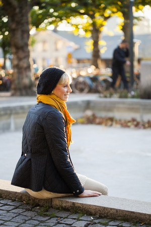 Young woman in warm clothing sitting on promenade