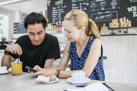 Happy multi-ethnic friends using phone at table in cafe