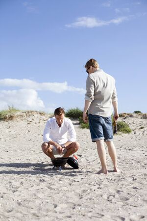 barbecues: Male friends looking at barbecue at beach