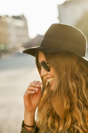 Happy woman in sunglasses at hat on street