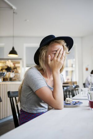 bashfulness: Young woman covering face with hand while sitting at restaurant table LANG_EVOIMAGES