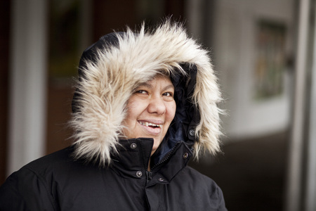 beings: Portrait of happy down syndrome woman in furry hood jacket