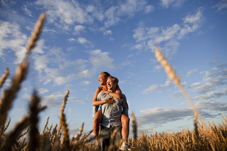 Happy young man piggybacking woman on wheat field