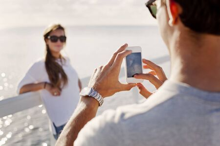 beings: Man photographing woman through smart phone on pier