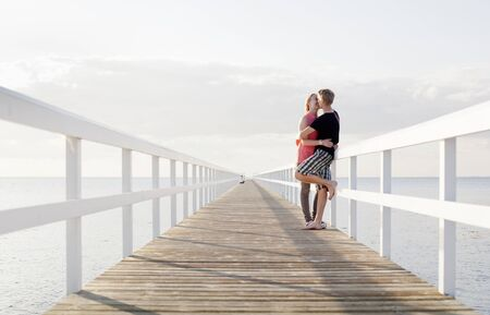 smooching: Romantic couple embracing on pier LANG_EVOIMAGES