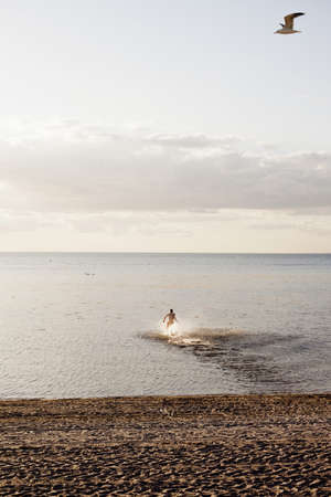beings: Man running into sea at beach