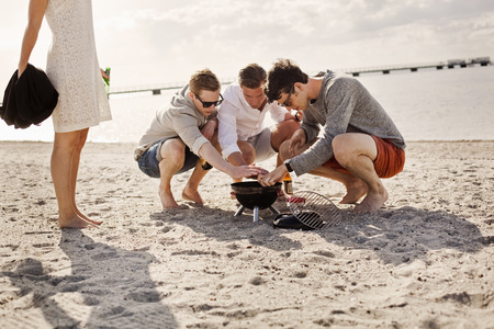beings: Male friends igniting barbeque grill by woman on beach