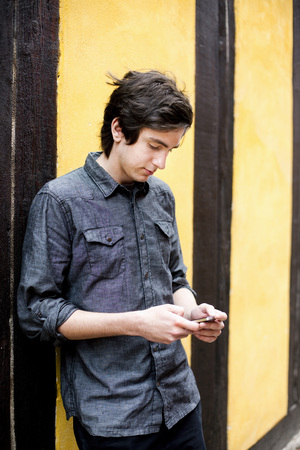 beings: Young man text messaging while leaning on wall