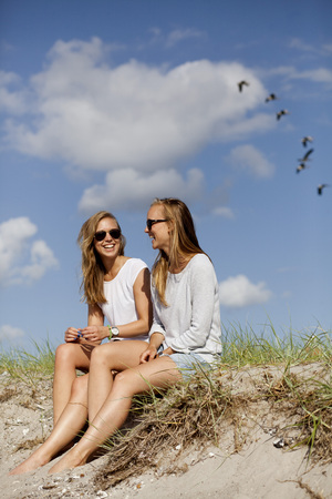 Happy female friends sitting on sand at beach LANG_EVOIMAGES