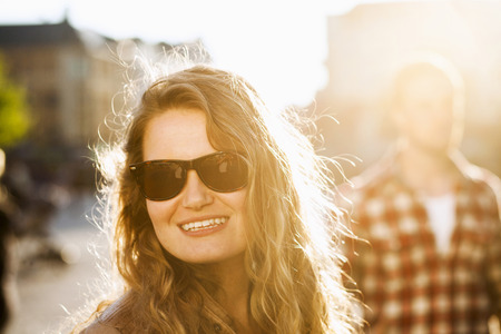 Happy young woman looking away while wearing sunglasses outdoors LANG_EVOIMAGES