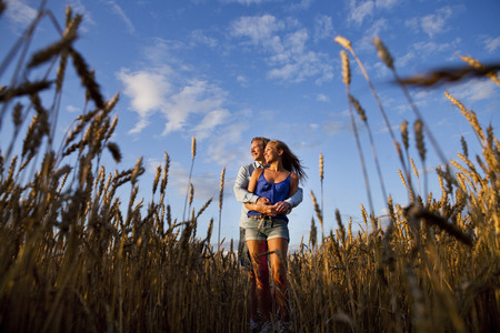 beings: Affectionate young couple embracing while standing on wheat field