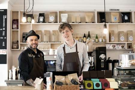 beings: Portrait of confident workers standing at cafe counter
