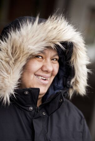 beings: Portrait of happy mentally disabled woman in furry hood jacket