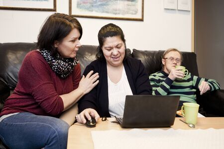 gente adulta: Mature woman assisting down syndrome female in using laptop while man having coffee in background