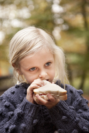 Girl eating sandwich outdoors LANG_EVOIMAGES