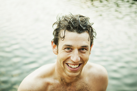 beings: Portrait of happy wet shirtless man against lake LANG_EVOIMAGES