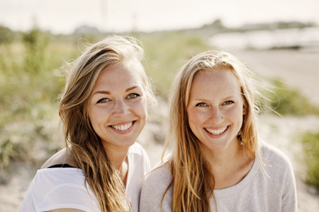 Portrait of female friends smiling at beach LANG_EVOIMAGES