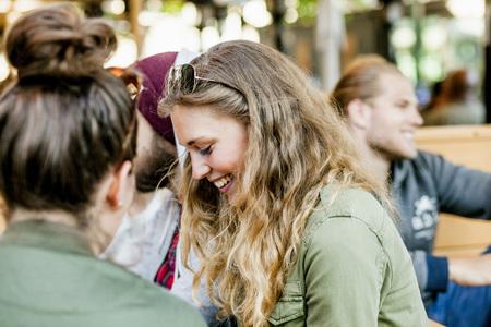 sidewalk talk: Side view of happy woman with friends at sidewalk cafe