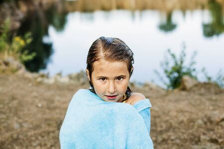 Portrait of girl wrapped in towel standing at lakeshore