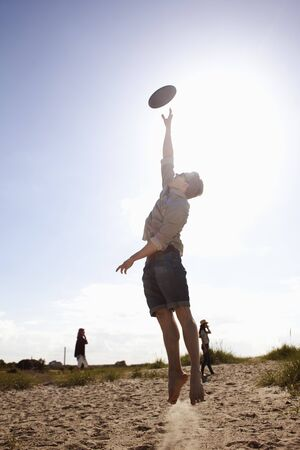 Young man in midair catching plastic disc
