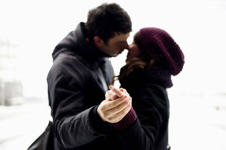 cherished: Side blurred view of young couple kissing against clear background
