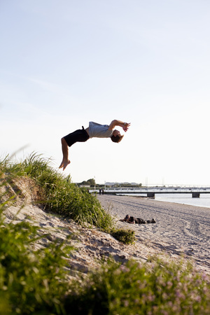 feats: Full length of young man doing backflip on beach