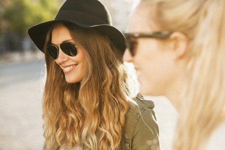 Happy woman in sunglasses at hat with friend on street