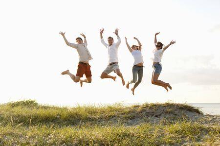 Full length of friends jumping on beach against sky