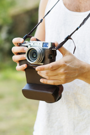 Midsection of man holding vintage camera at park LANG_EVOIMAGES