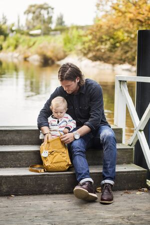 Full length of father searching something in backpack while sitting with baby girl on steps at lakeshore LANG_EVOIMAGES