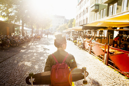 Rear view of woman with skateboard and backpack walking on street by sidewalk cafe LANG_EVOIMAGES