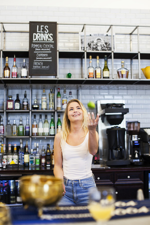 beings: Happy female bartender tossing apple at cafe counter