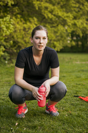 take a breather: Full length of tired young woman holding water bottle while crouching in park