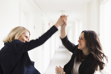beings: Successful businesswomen giving high-five in office