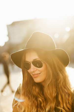 Smiling young woman in sunglasses at hat on street LANG_EVOIMAGES