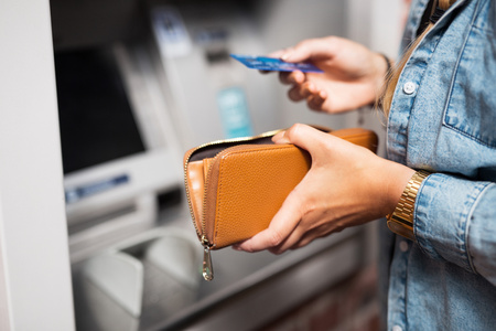 withdrawing: Woman withdrawing money from ATM LANG_EVOIMAGES
