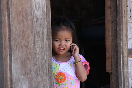 tat: young girl in wooden house by opening Tat Lo Bolaven Plateau Laos
