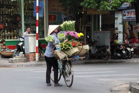 merchant: Flower merchant with bike in the streets of Hanoi, Vietnam