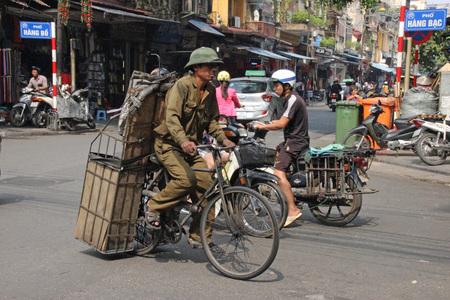 streetlife: Vietnamese soldier, riding his bike in Hanoi, Vietnam