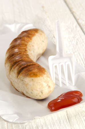 german bratwurst with ketchup on a paper plate photo