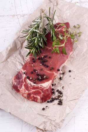 sirloin steak: sirloin steak on white paper with herbs and spice Stock Photo