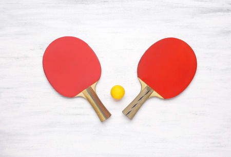 tabletennis: Two table tennis rackets on a white wooden table. Top view of table tennis paddles. Competition concept. Stock Photo