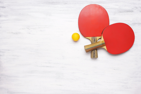 tabletennis: Two table tennis rackets on a white wooden table. Top view of   paddles. Competition concept.