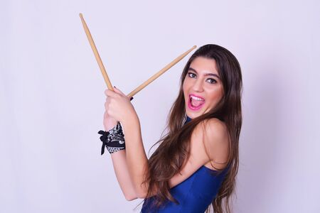 drum sticks: Stylish caucasian young woman holding drum sticks, isolated over grey background. Urban and rock concept. Girl power. Stock Photo