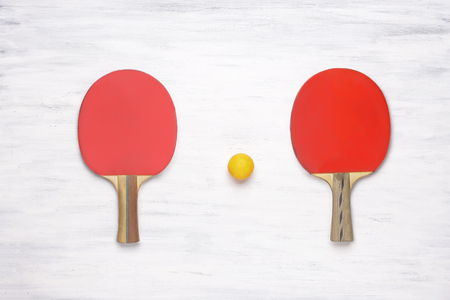 tabletennis: Two table tennis rackets on a white wooden table. Top view of ping pong paddles. Competition concept.